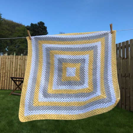 Crochet baby blanket in yellow white and grey