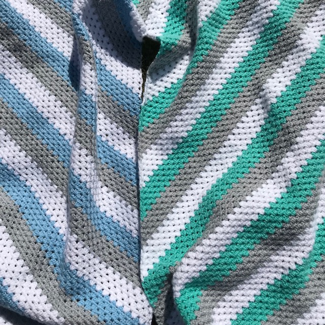 Close up of granny stitch crochet blankets in grey, white, blue and green