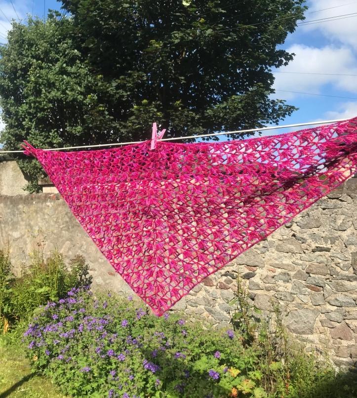 Finished crochet shawl hanging on washing line