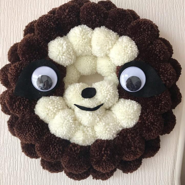 Pompom wreath designed as a sloth